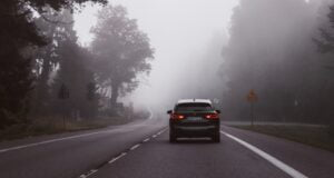 Car on an empty road with mist and trees in the background.